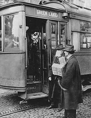 Streetcar conductor checks passengers for masks